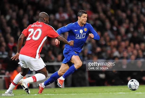 Manchester United's Portuguese midfielder Cristiano Ronaldo tussles with Arsenal's Swiss defender Johan Djourou during their UEFA Champions League...