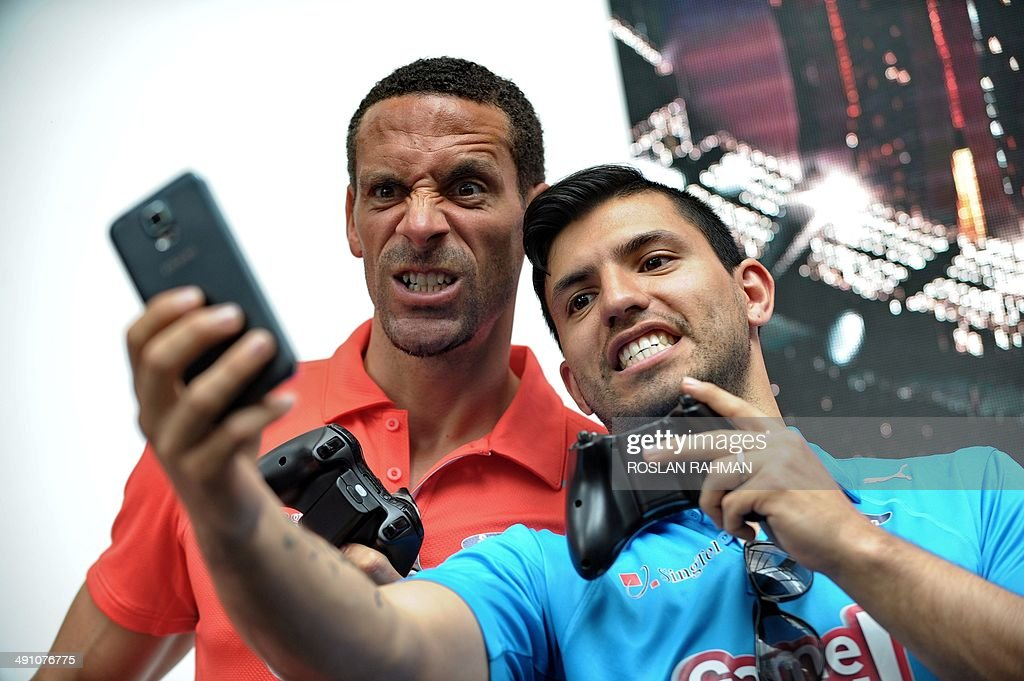 Manchester United's Rio Ferdinand (L) and Manchester City's Sergio Aguero pose for a selfie during the football carnival at Raffles place financial district in Singapore on May 16, 2014 for the SG Game ON! Ultimate Selfie Challenge. SG Game On! is a two-day contest aimed at celebrating Singapore's passion for football in the lead up to the 2014 FIFA World Cup. AFP PHOTO/ROSLAN RAHMAN