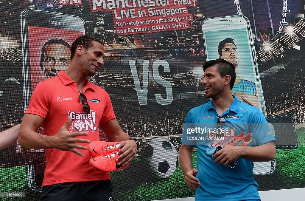 Manchester United's Rio Ferdinand (L) and Manchester City's Sergio Aguero (R) attend the football carnival at Raffles place financial district in Singapore on May 16, 2014 for the SG Game ON! Ultimate Selfie Challenge. SG Game On! is a two-day contest aimed at celebrating Singapore's passion for football in the lead up to the 2014 FIFA World Cup.