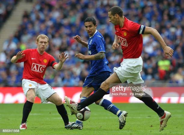 Manchester United's Rio Ferdinand and Paul Scholes battle for the ball with Everton's Tim Cahill