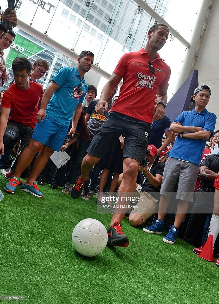 Manchester United's Rio Ferdinand (front) closes his eyes as he kick the ball while Manchester City's Sergio Aguero (behind) looks on at the football carnival at Raffles place financial district in Singapore on May 16, 2014 for the SG Game ON! Ultimate Selfie Challenge. SG Game On! is a two-day contest aimed at celebrating Singapore's passion for football in the lead up to the 2014 FIFA World Cup.