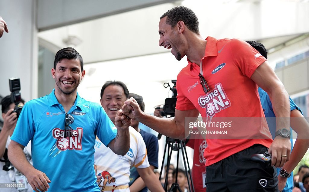 Manchester United's Rio Ferdinand (R) gives a fist bump to Manchester City's Sergio Aguero (L) during a video console game at the Football carnival at Raffles place financial district in Singapore on May 16, 2014 for the SG Game ON! Ultimate Selfie Challenge. SG Game On! is a two-day contest aimed at celebrating Singapore's passion for football in the lead up to the 2014 FIFA World Cup.