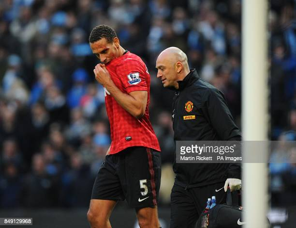Manchester United's Rio Ferdinand receives medical treatment to a cut on his head after being struck by an object thrown from the crowd