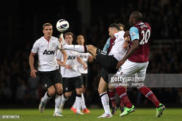 Manchester United's Ryan Giggs battles for the ball with West Ham United's Guy Demel
