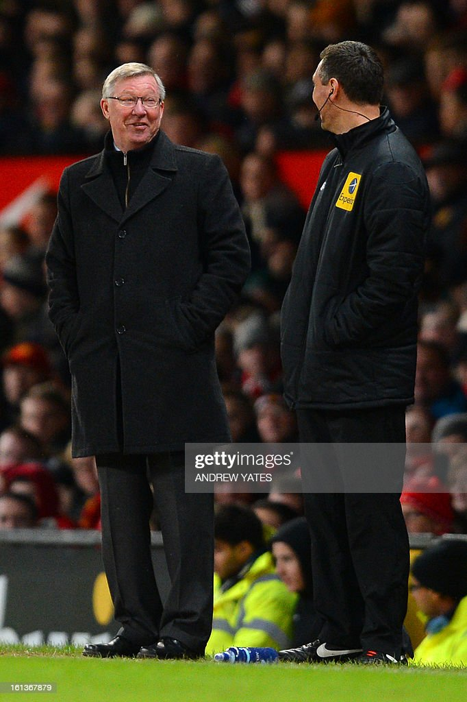 """Manchester United's Scottish manager Alex Ferguson (L) and fourth official Andre Marriner (R) talk during the English Premier League football match between Manchester United and Everton at Old Trafford, Manchester, North West England, on February 10, 2013. Manchester United won the match 2-0 to secure a 12 point lead at the top of the Premier League table. USE. No use with unauthorized audio, video, data, fixture lists, club/league logos or """"live"""" services. Online in-match use limited to 45 images, no video emulation. No use in betting, games or single club/league/player publications."""