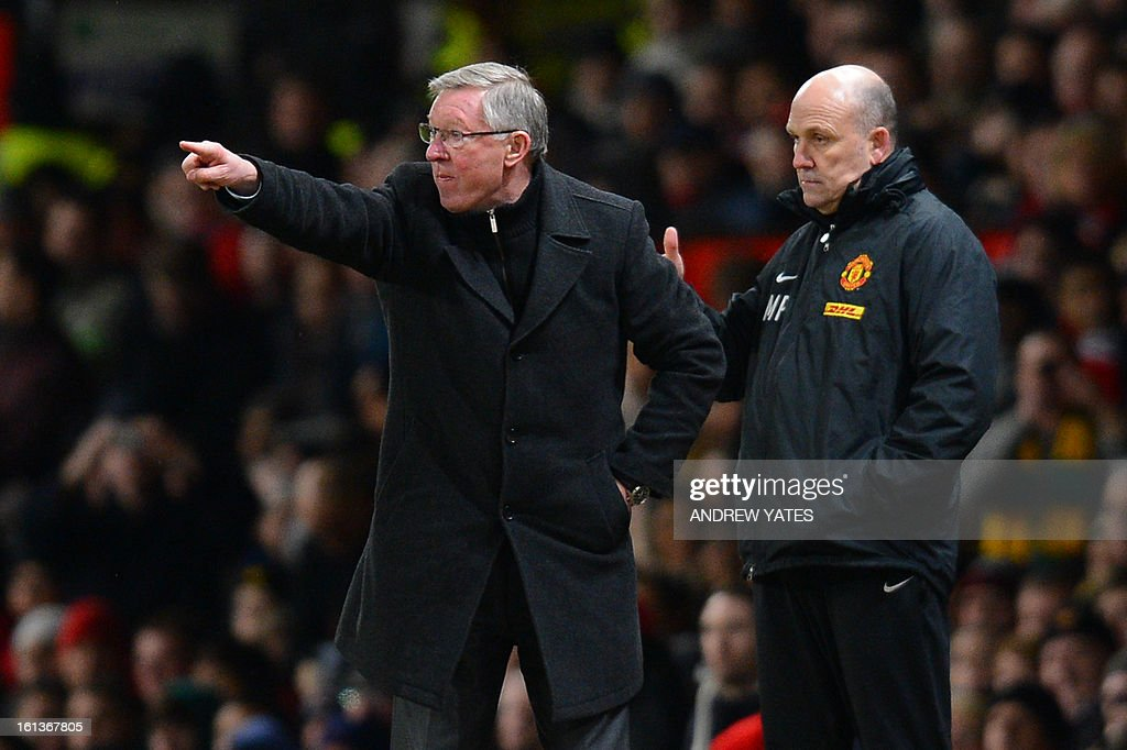 """Manchester United's Scottish manager Alex Ferguson (L) and Manchester United's assistant manager Mick Phelan (R) gesture from the touchline during the English Premier League football match between Manchester United and Everton at Old Trafford, Manchester, North West England, on February 10, 2013. AFP PHOTO / ANDREW YATES USE. No use with unauthorized audio, video, data, fixture lists, club/league logos or """"live"""" services. Online in-match use limited to 45 images, no video emulation. No use in betting, games or single club/league/player publications."""