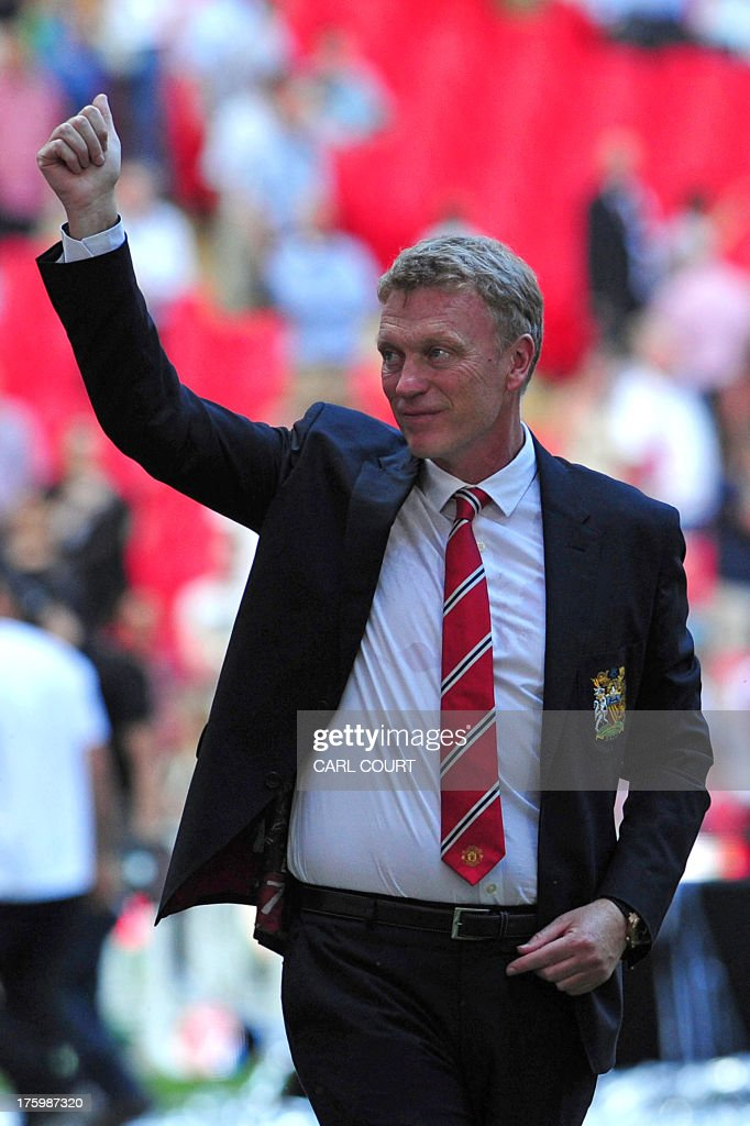 Manchester United's Scottish manager David Moyes gives a thumbs up as Manchester United celebrate after beating Wigan Athletic the FA Community Shield football match between Manchester United and Wigan Athletic at Wembley Stadium in north London on August 11, 2013. Manchester United's Dutch striker Robin van Persie scored both goals in their 2-0 victory.