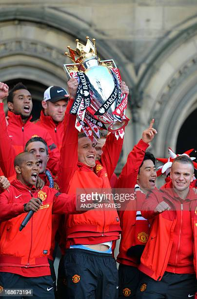 Manchester United's Serbian defender Nemanja Vidic holds the trophy as the team arrives in an opentopped bus outside town hall in Manchester north...