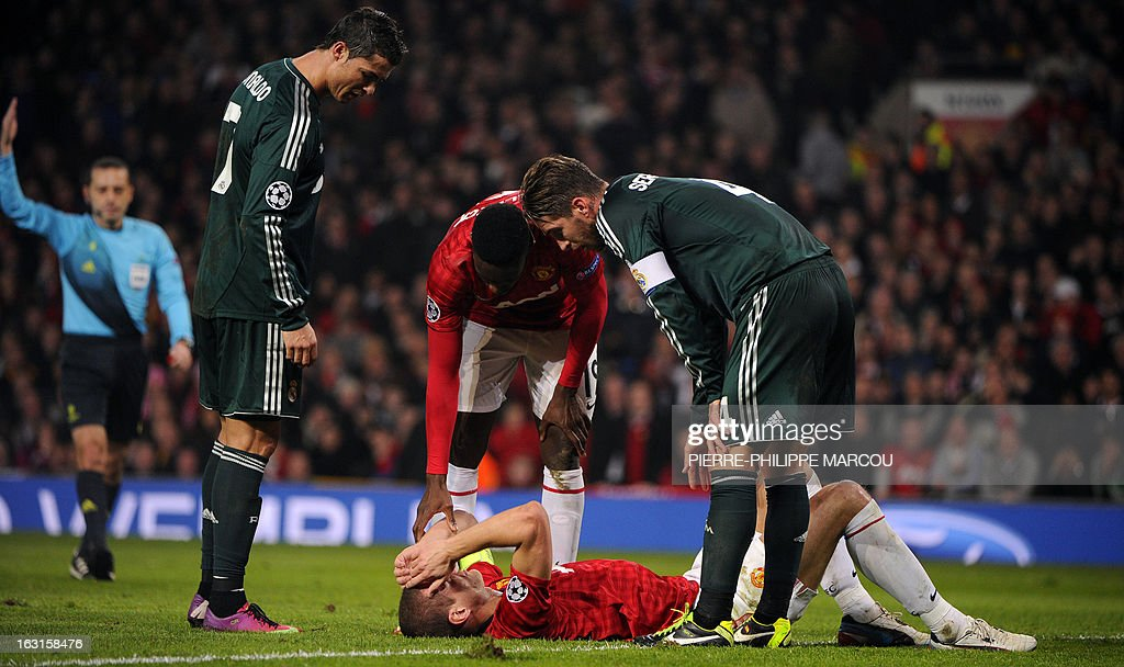Manchester United's Serbian defender Nemanja Vidic (floor) lies injured after colliding with Real Madrid goalkeeper Diego Lopez as Real Madrid's Portuguese forward Cristiano Ronaldo (L) and Manchester United's English striker Danny Welbeck (C) look on during the UEFA Champions League round of 16 second leg football match between Manchester United and Real Madrid at Old Trafford in Manchester, northwest England on March 5, 2013.