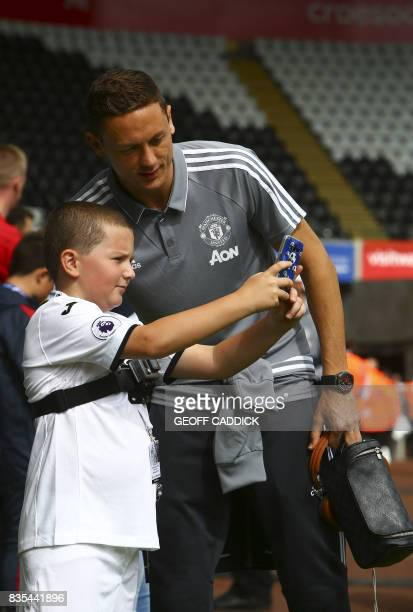 Manchester United's Serbian midfielder Nemanja Matic has a photograph taken with a young fan on his arrival for the English Premier League football...