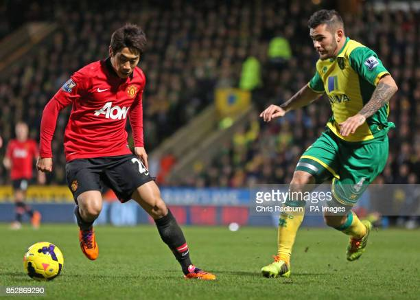 Manchester United's Shinji Kagawa is challenged by Norwich City's Bradley Johnson during the Barclays Premiership match at Carrow Road Norwich