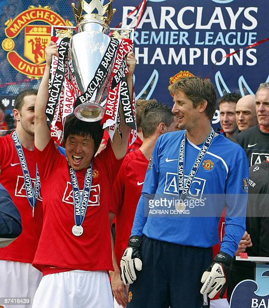 Manchester United's South Korean midfielder JiSung Park and Dutch goalkeeper Edwin van der Sar celebrate with the English Premier League trophy after...