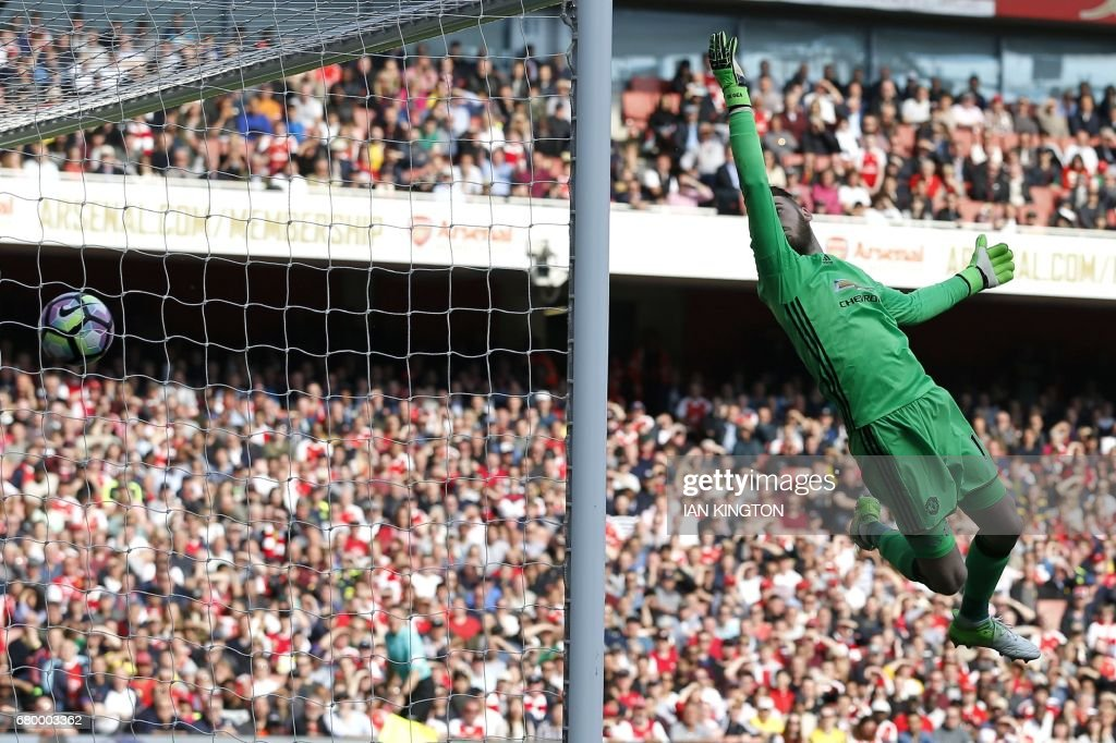 Manchester United's Spanish goalkeeper David de Gea cannot prevent Arsenal's Swiss midfielder Granit Xhaka's deflected shot beating him for the opening goal of the English Premier League football match between Arsenal and Manchester United at the Emirates Stadium in London on May 7, 2017. / AFP PHOTO / IKIMAGES / Ian KINGTON / RESTRICTED TO EDITORIAL USE. No use with unauthorized audio, video, data, fixture lists, club/league logos or 'live' services. Online in-match use limited to 45 images, no video emulation. No use in betting, games or single club/league/player publications. /