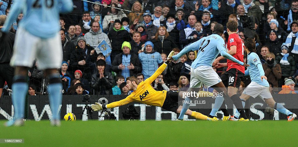 """Manchester United's Spanish goalkeeper David de Gea (C) dives but cannot reach the shot from Manchester City's Ivorian midfielder Yaya Toure (3rd R) during the English Premier League football match between Manchester City and Manchester United at The Etihad stadium in Manchester, north-west England on December 9, 2012. USE. No use with unauthorized audio, video, data, fixture lists, club/league logos or """"live"""" services. Online in-match use limited to 45 images, no video emulation. No use in betting, games or single club/league/player publications."""