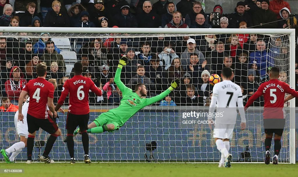 Manchester United's Spanish goalkeeper David de Gea (C) dives but fails to save a shot from Swansea City's Dutch defender Mike van der Hoorn (L) as he scores his team's first goal during the English Premier League football match between Swansea City and Manchester United at The Liberty Stadium in Swansea, south Wales on November 6, 2016. / AFP / Geoff CADDICK / RESTRICTED TO EDITORIAL USE. No use with unauthorized audio, video, data, fixture lists, club/league logos or 'live' services. Online in-match use limited to 75 images, no video emulation. No use in betting, games or single club/league/player publications. /