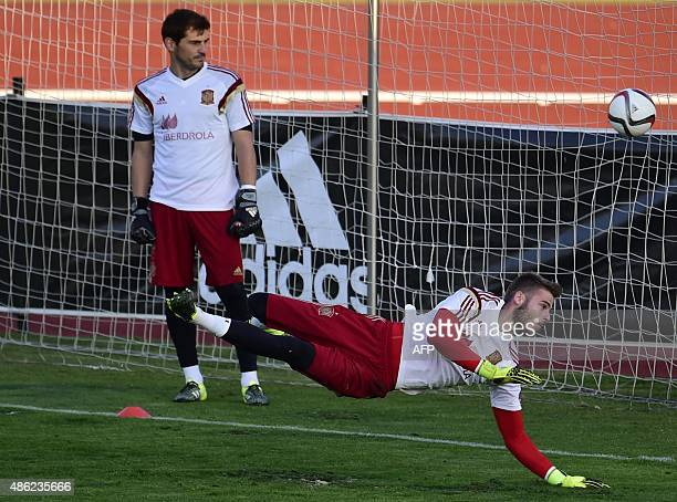 Manchester United's Spanish goalkeeper David de Gea dives for a ball as Porto FC's Spanish goalkeeper Iker Casillas trains with the Spanish national...