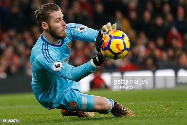 Manchester United's Spanish goalkeeper David de Gea dives to save a shot from Arsenal's Germanborn Bosnian defender Sead Kolasinac during the English...