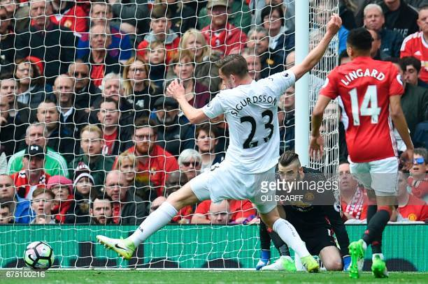 Manchester United's Spanish goalkeeper David de Gea watches as the rebound from his save just goes just beyond the reach of Swansea City's Icelandic...