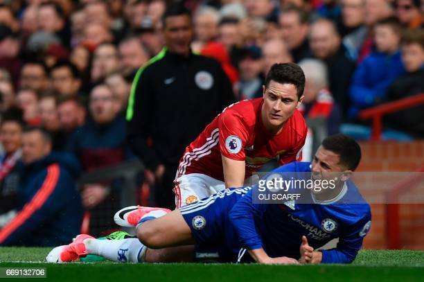 Manchester United's Spanish midfielder Ander Herrera goes down in a challenge with Chelsea's Belgian midfielder Eden Hazard during the English...