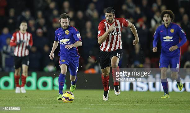 Manchester United's Spanish midfielder Juan Mata runs with the ball chased by Southampton's Italian striker Graziano Pelle during the English Premier...