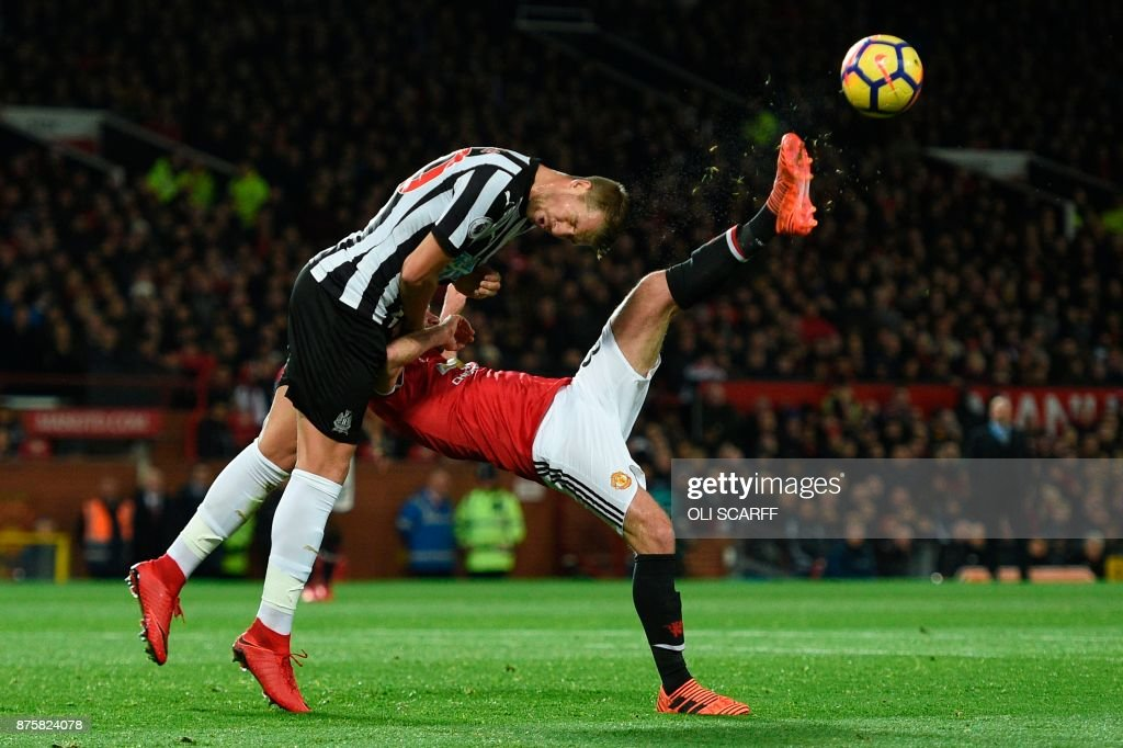 TOPSHOT - Manchester United's Spanish midfielder Juan Mata (R) tries an overhead kick as Newcastle United's French midfiielder Florian Lejeune (L) goes for a header during the English Premier League football match between Manchester United and Newcastle at Old Trafford in Manchester, north west England, on November 18, 2017. / AFP PHOTO / Oli SCARFF / RESTRICTED TO EDITORIAL USE. No use with unauthorized audio, video, data, fixture lists, club/league logos or 'live' services. Online in-match use limited to 75 images, no video emulation. No use in betting, games or single club/league/player publications. /