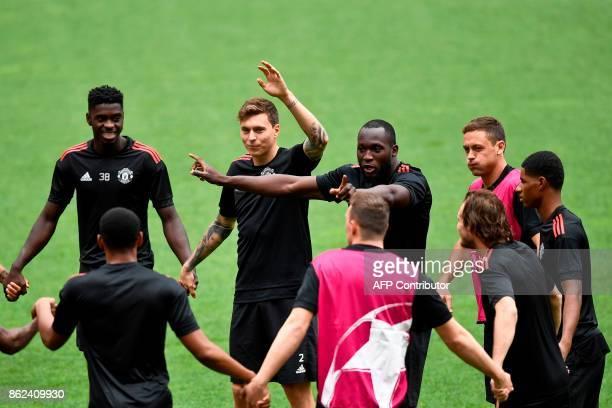 Manchester United's Swedish defender Victor Lindelof gestures next to teammates Manchester United's defender Axel Tuanzebe Manchester United's...