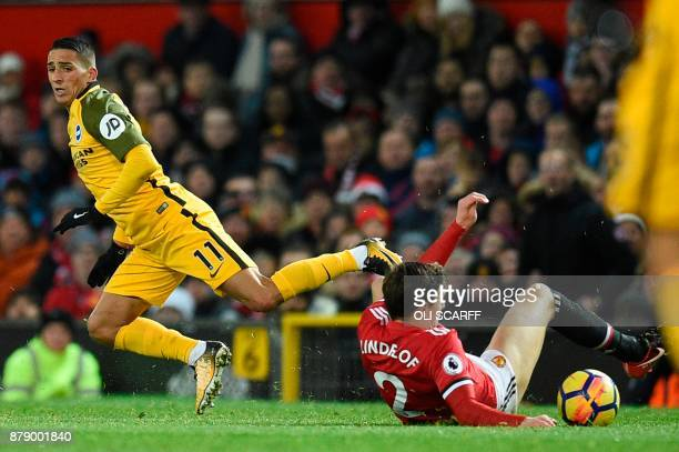 Manchester United's Swedish defender Victor Lindelof tackles Brighton's French midfielder Anthony Knockaert during the English Premier League...