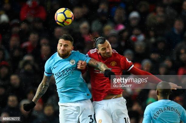 Manchester United's Swedish striker Zlatan Ibrahimovic challenges Manchester City's Argentinian defender Nicolas Otamendi in the air during the...