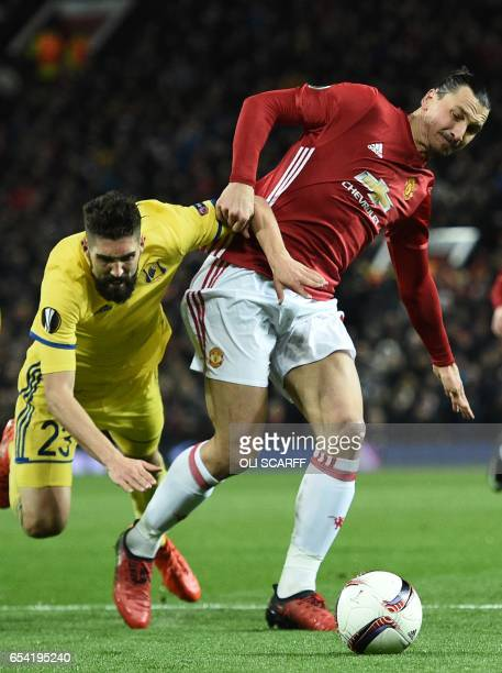 Manchester United's Swedish striker Zlatan Ibrahimovic holds off Rostov's Slovanian defender Miha Mevlja to make a run during the UEFA Europa League...