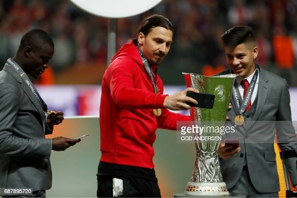 Manchester United's Swedish striker Zlatan Ibrahimovic takes a photo of the trophy with Manchester United's Argentinian defender Marcos Rojo and...