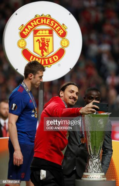 Manchester United's Swedish striker Zlatan Ibrahimovic takes a photo of the trophy with Manchester United's Ivorian defender Eric Bailly after the...