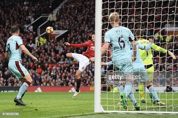 Manchester United's Swedish striker Zlatan Ibrahimovic volleys the ball to draw a save from Burnley's English goalkeeper Tom Heaton during the...