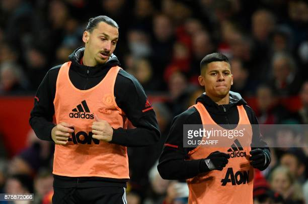Manchester United's Swedish striker Zlatan Ibrahimovic warms up with Manchester United's Argentinian defender Marcos Rojo on the touchline during the...
