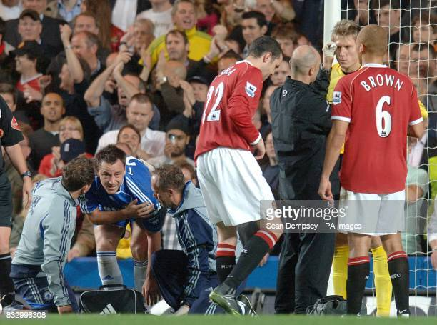Manchester United's Tomasz Kuszczak and Chelsea's John Terry both receive treatment following a challenge