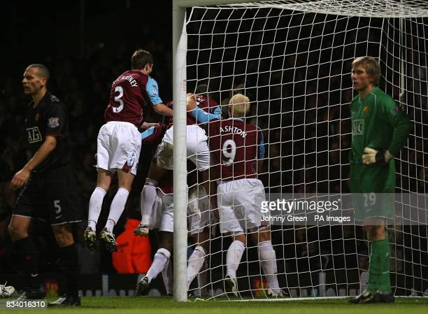 Manchester United's Tomasz Kuszczak and Rio Ferdinand stand dejected as West Ham United's Matthew Upson celebrates scoring his sides second goal with...