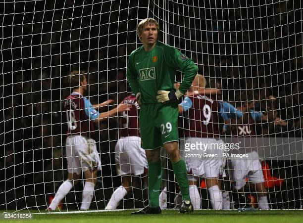 Manchester United's Tomasz Kuszczak stands dejected as West Ham United players celebrate Matthew Upson scoring their second goal of the match