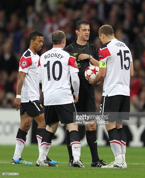 Manchester United's Wayne Rooney and Nemanja Vidic surround referee Viktor Kassai