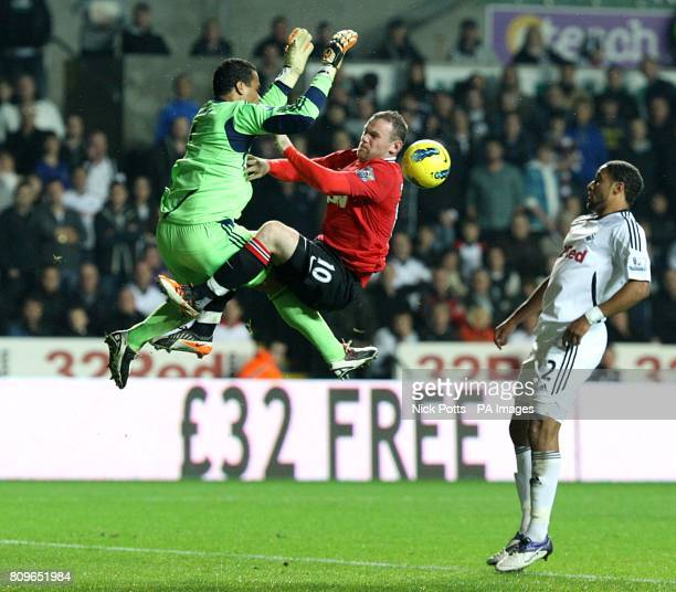 Manchester United's Wayne Rooney and Swansea City goalkeeper Michel Vorm collide as they go for a high ball into the Swansea box
