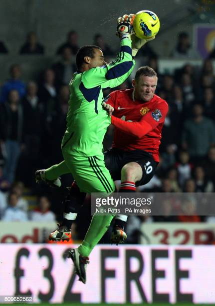Manchester United's Wayne Rooney and Swansea City goalkeeper Michel Vorm collide as they go for a high ball during the Barclays Premier League match...