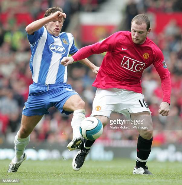 Manchester United's Wayne Rooney and Wigan Athletic's Michael Brown battle for the ball