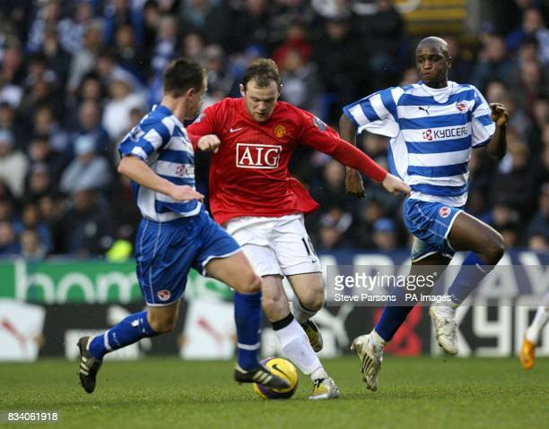 Manchester United's Wayne Rooney attempts to get past two Reading players
