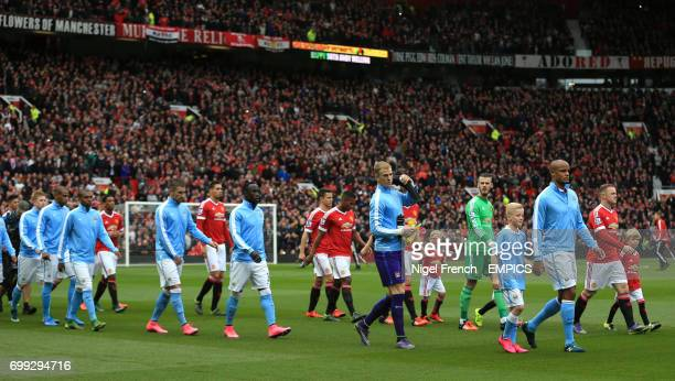 Manchester United's Wayne Rooney captain and Manchester City's Vincent Kompany captain lead their teams out at Old Trafford