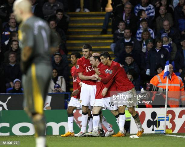 Manchester United's Wayne Rooney celebrates his goal with teammates as Reading goalkeeper Marcus Hahnemann stands dejected