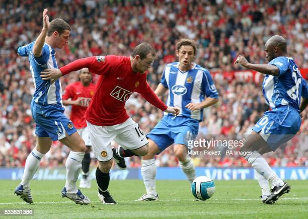 Manchester United's Wayne Rooney holds off Wigan Athletic's Jason Koumas Michael Brown and Salomon Olembe as they battle for the ball
