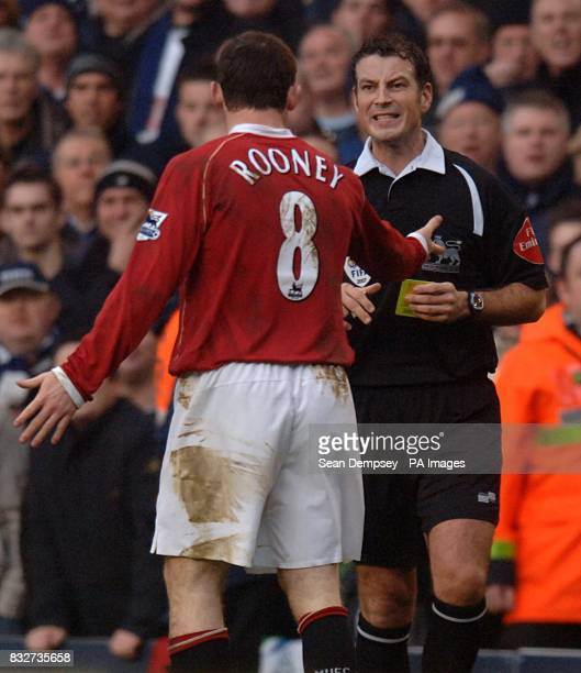 Manchester United's Wayne Rooney is booked by referee Mark Clattenburg