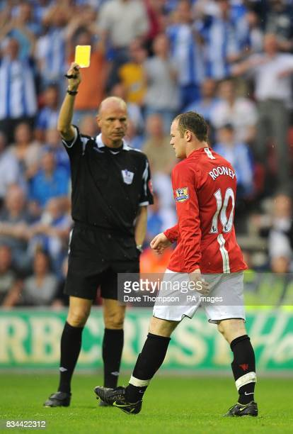 Manchester United's Wayne Rooney is booked by referee Steve Bennett