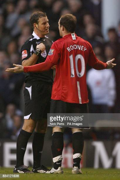 Manchester United's Wayne Rooney pleads to referee Mark Clattenburg after he was booked for diving