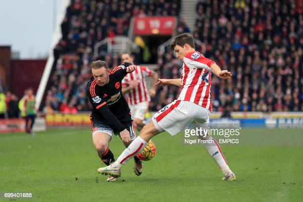 Manchester United's Wayne Rooney trips over a challenge from Stoke City's Philipp Wollscheid