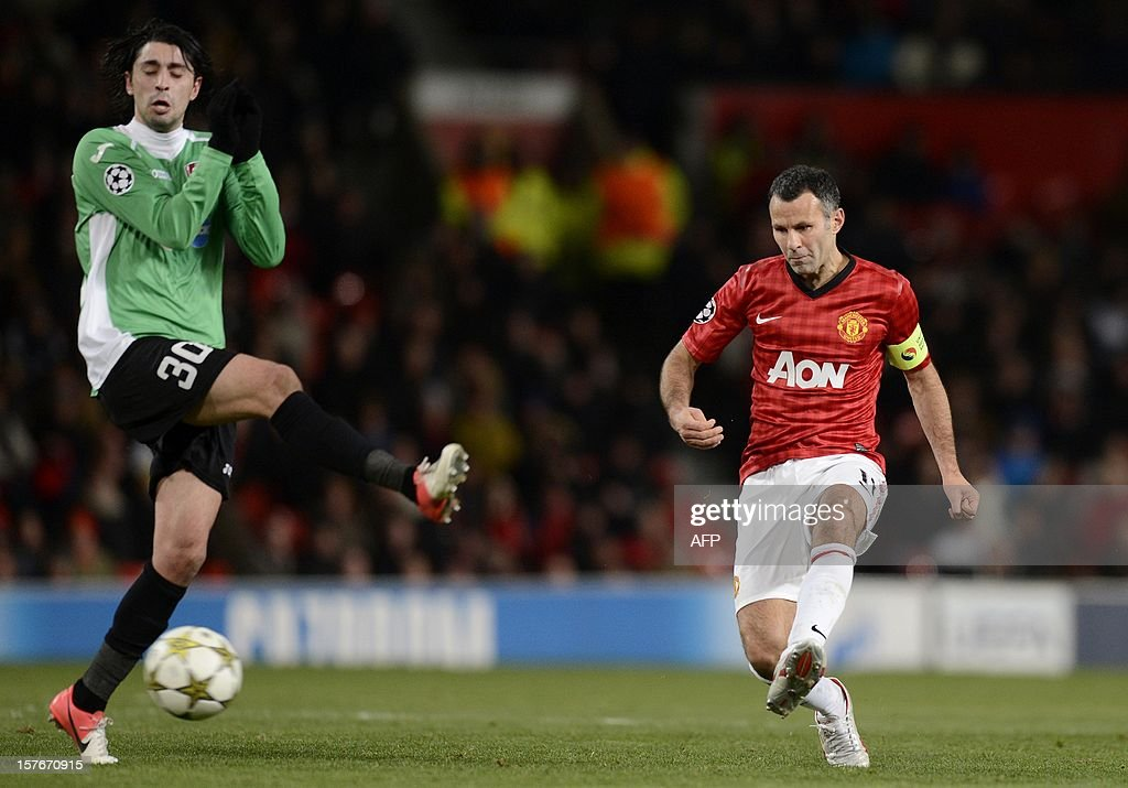 Manchester United's Welsh midfielder Ryan Giggs (R) shoots past Cluj's Portugese midfielder Rui Pedro during the UEFA Champions League group H football match between Manchester United and CFR Cluj-Napoca at Old Trafford in Manchester, north-west England, on December 5, 2012 CFR Cluj-Napoca won 1-0.