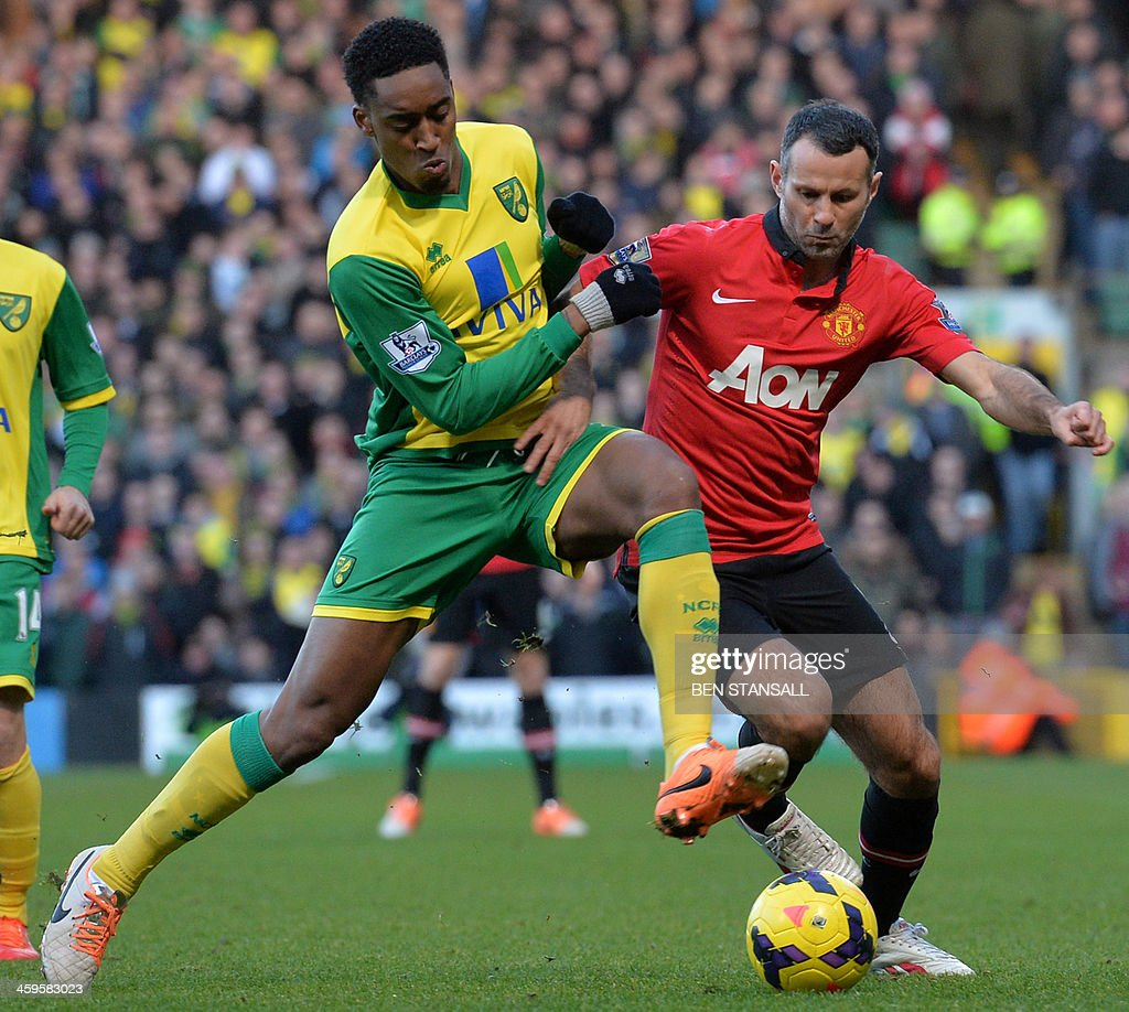 Manchester United's Welsh midfielder Ryan Giggs (R) vies for the ball with Norwich City's Dutch midfielder Leroy Fer (L) during the English Premier League football match between Norwich City and Manchester United at Carrow Road stadium in Norwich, eastern England, on December 28, 2013. AFP PHOTO / BEN STANSALL USE. No use with unauthorized audio, video, data, fixture lists, club/league logos or live services. Online in-match use limited to 45 images, no video emulation. No use in betting, games or single club/league/player publications.